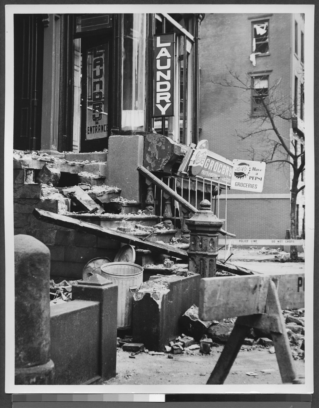 Close-up of corner of Seventh Avenue and Sterling Place after crash of United Airlines airplane with damaged building in foreground with signs.